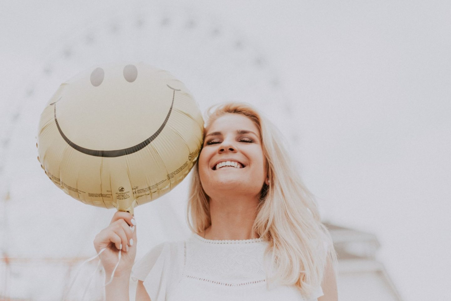 a woman smiling with a balloon despite her day going all wrong.