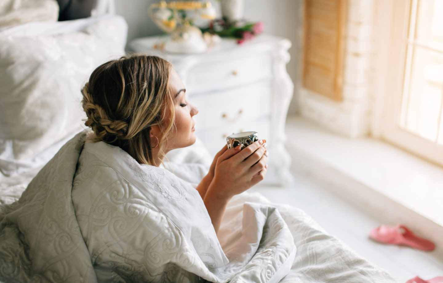 woman drinking coffee in bed.