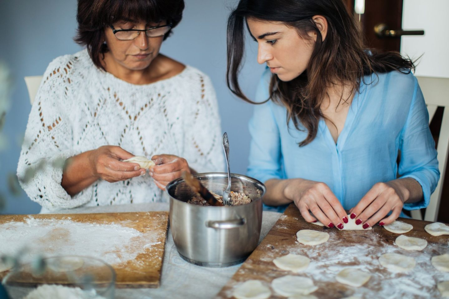 Mother and daughter making dumplings together.